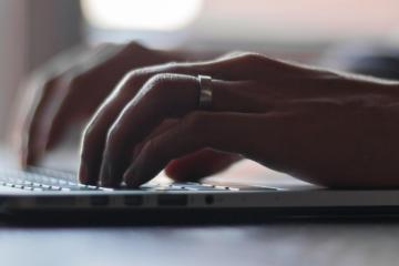 Man typt seo teksten op een laptop